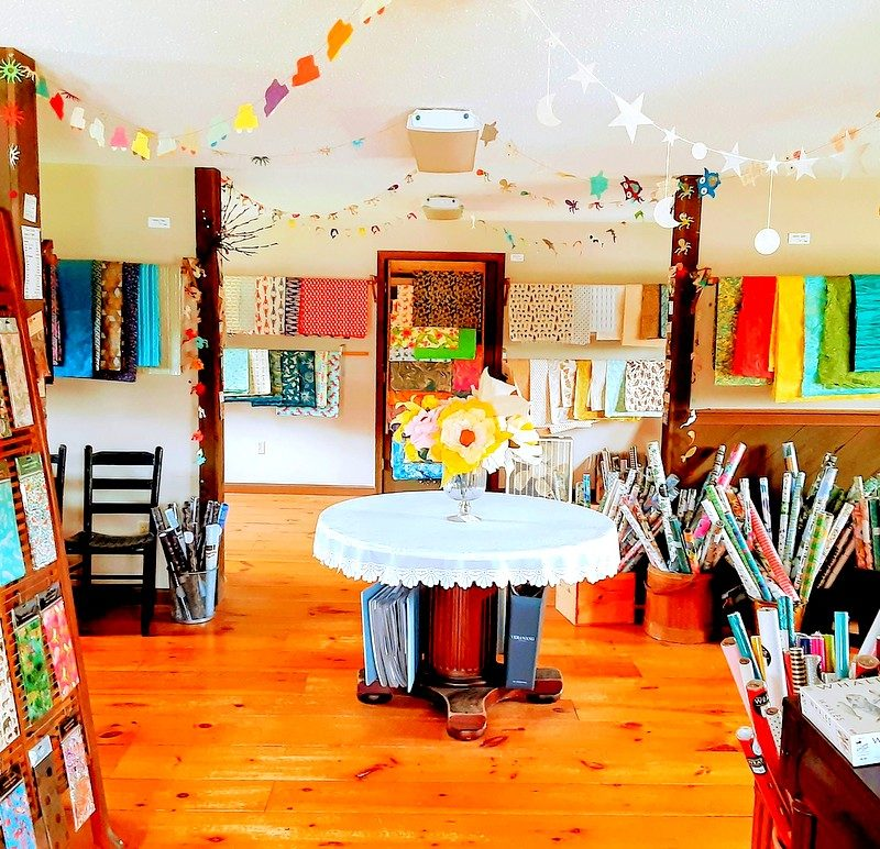 The interior of a materials and cards shop is shown
